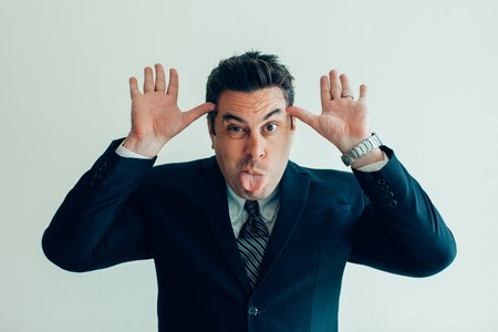 Funny businessman grimacing and sticking tongue Stock Photo