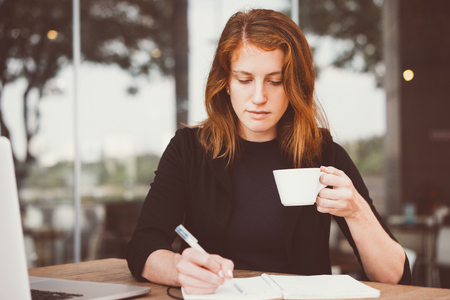Serious Student with Coffee Cup Writing Notes
