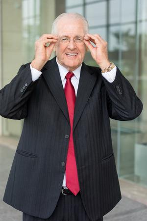 Smiling Senior Business Leader Adjusting Glasses