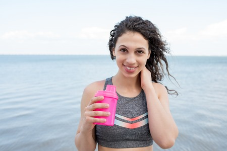 Closeup of smiling sporty Caucasian girl holding pink shaker with calm sea in background. Tired female athlete drinking water after street workout. Fitness and sport nutrition concept