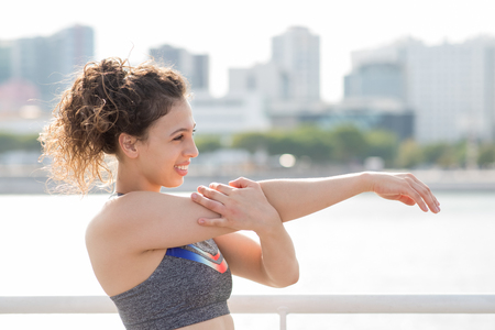 Closeup of happy sporty girl in sport bra preparing for training and warming up shoulders on city quay. Positive student keeping fit with street workout. Sport and fitness anywhere concept