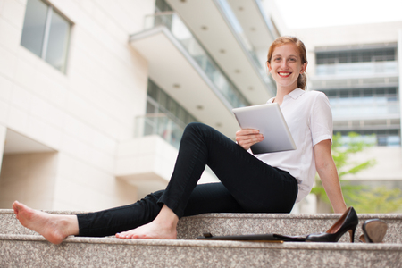 Portrait of happy young Caucasian businesswoman or student sitting barefoot with digital tablet, looking at camera and smiling outdoors. Life work balance concept
