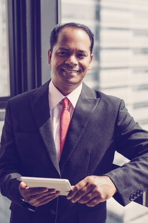 Portrait of successful mid adult Indian businessman wearing suit standing at window holding digital tablet, looking at camera and smiling 版權商用圖片
