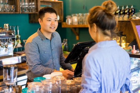 Positive confident cashier taking customers order and asking about preferences. Smiling handsome young staff friendly talking to client. Coffee shop company concept Stock fotó