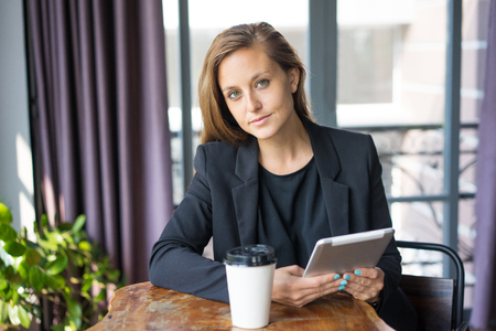 Closeup portrait of confident young beautiful business woman looking at camera, holding tablet computer and sitting at cafe table with window in background. Break concept. Front view.