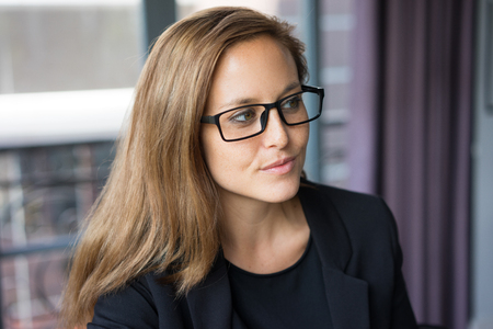 Closeup portrait of serious young beautiful brown-haired woman looking away with window in background. Beautiful business woman concept. Stock Photo