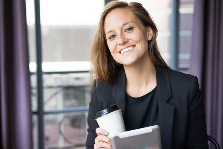 Closeup portrait of smiling young beautiful business woman looking at camera, holding tablet computer and drink with window in background. Break concept. Front view. Stock Photo
