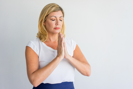 Calm businesswoman relaxing while meditating and joining hands in mudra. Serious attractive woman relaxing. Tranquility concept