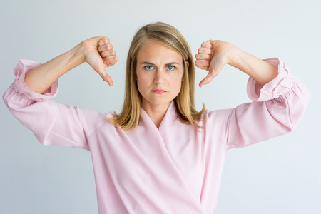 Displeased business lady showing thumbs down and looking at camera. Upset disappointed woman gesturing and giving negative assessment. Disapproval concept Stock Photo