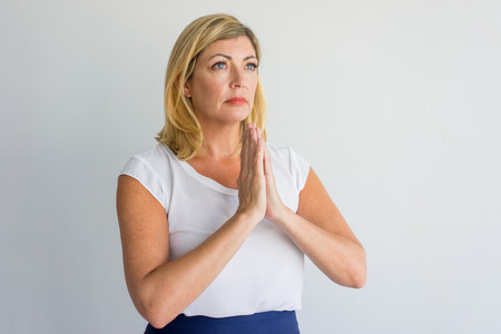 Serious sad mature woman praying about success and asking about solution. Pensive lady meditating and holding hands in mudra. Lifestyle concept