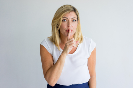 Serious mature woman asking to be quiet and making shh gesture. Beautiful teacher keeping calm about secret. Privacy concept