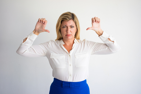 Angry mature Caucasian woman in formal blouse showing thumbs down. Annoyed boss dissatisfied with employees work. Business failure and displeasure concept.
