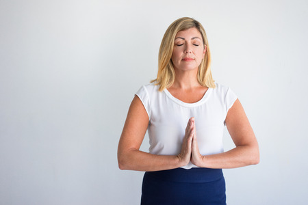 Happy middle aged Caucasian woman with closed eyes putting hands together in meditation. Office employee practicing breathing exercises on break. Meditation or life and work balance success concept Banque d'images