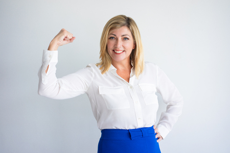 Smiling mature Caucasian woman in formal blouse flexing bicep. Positive experienced businesswoman or expert illustrating power and professional confidence. Business success and strength concept