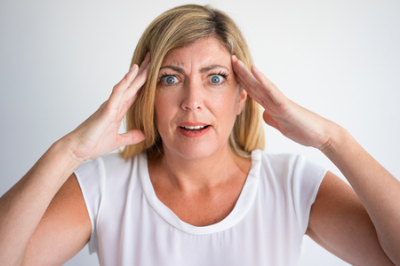 Zszokowana dojrzała kobieta rasy białej z szeroko otwartymi oczami i pytającą twarzą dotykającą skroni. Zbliżenie gniewnej pani nie może uwierzyć własnym oczom. Złe wieści lub koncepcja niespodzianki