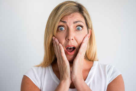 Shocked mature Caucasian woman with open mouth covering cheeks with hands. Client discovering losses caused by bad company service. Bad news or failure, concept