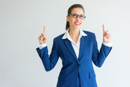 Cheerful enterprising young businesswoman pointing up. Positive successful Caucasian business expert standing against white background. Idea concept