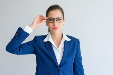 Confident beautiful young businesswoman adjusting glasses. Serious purposeful Caucasian female business executive looking at camera. Leadership concept Stock Photo