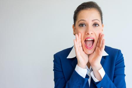 Mujer de negocios feliz gritando en voz alta. Primer de la mujer caucásica joven y hermosa en traje formal que grita y que anuncia algo con la boca abierta. Concepto de negocios y noticias de última hora