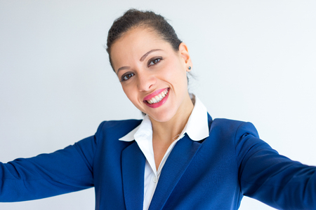 Selfie of smiling young Caucasian woman in formal suit. Businesswoman taking self portrait and holding camera with both hands. Business and photo concept Archivio Fotografico