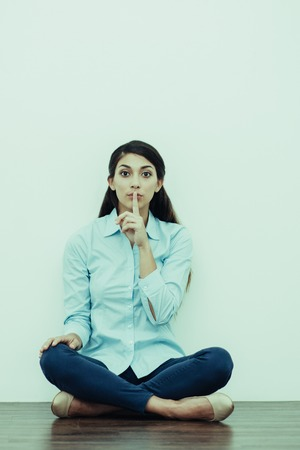 Portrait of serious young woman sitting on floor with crossed legs, looking straight and making silence gesture with white wall in background. Front view.