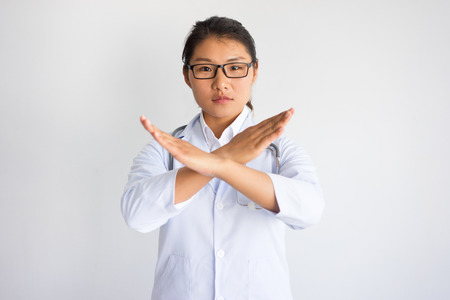 Serious Asian female doctor showing crossed hands. Medical constraints concept. Isolated front closeup view on white background.