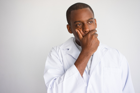 Portrait of upset African man in white coat. Frustrated doctor covering mouth with hand. Bad news and medicine concept