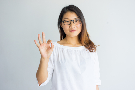 Content pretty Asian girl with highlighted hair making ok sign as symbol of approval. Confident attractive young woman in eyeglasses looking at camera. Student concept