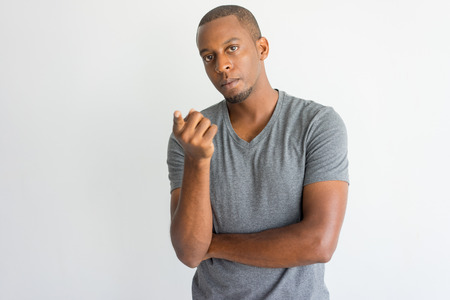Serious uncertain handsome African guy pointing at camera while asking question. Misunderstanding young man with beard wearing t-shirt looking at camera. Problem concept Banque d'images