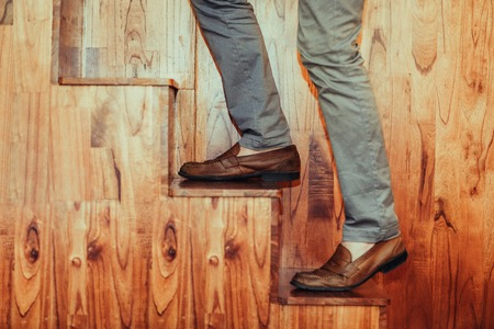 Cropped image of legs of man climbing wooden stairs. Side view.