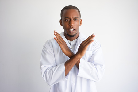 Serious black male doctor showing crossed hands. Medical constraints concept. Isolated front closeup view on white background. Stockfoto