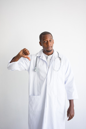 Serious black male doctor showing thumb down. Harm to health concept. Isolated front view on white background.