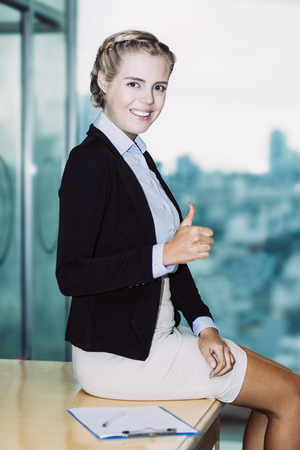 Portrait of positive confident beautiful young business woman looking at camera, showing thumb up and sitting on café table with big window in background Imagens