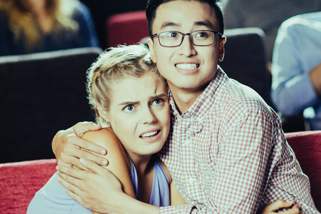 Portrait of scared multiethnic young couple, Asian man and Caucasian woman, sitting in cinema, watching horror and hugging in fear Stock Photo