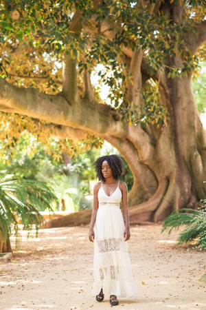 Serious attractive young black woman walking in park with big tree in background. Park relaxation concept. Front full length view.