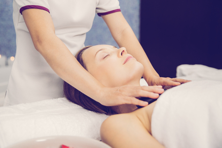 Content young woman closing eyes, lying on table and having stone massage therapy of chest in spa salon room Stock Photo