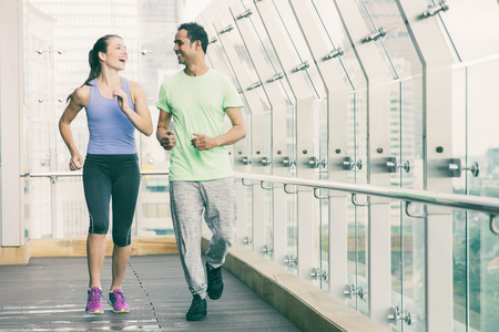 Smiling and laughing young man and woman wearing sportswear and jogging on terrace with glass fence and view of city outside