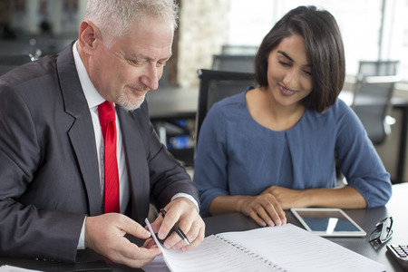 Content coach reviewing notes of female company newcomer. Middle aged man in tie and young Indian woman in casual wear thumbing notebook in coworking space. Business coaching and mentorship concept