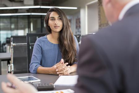 Reunión centrada en la clienta india con el asesor financiero. Candidato hermoso joven en la entrevista de trabajo en el espacio de oficina moderno. Concepto de consultoría o empleo empresarial