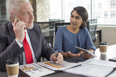 Young business expert annoyed with phone talk of her colleague during meeting. Mid adult man in formal wear speaking on phone, Indian woman looking at him with questioning face. Communication concept Stock Photo