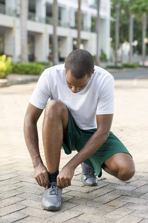 Black tourist keeping fit on vacation. Young Afro American man lacing up sneakers before running outdoors. Street workout concept