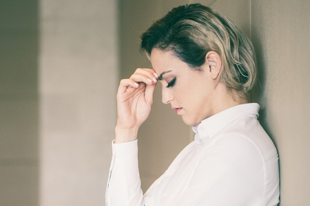 Closeup portrait of serious middle-aged businesswoman thinking hard, touching forehead, closing eyes and leaning on wall. Side view. Stock Photo
