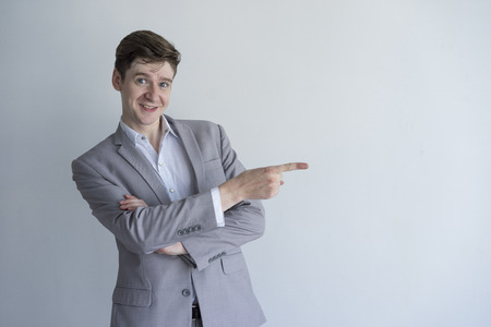 Positive enterprising male manager pointing aside and looking at camera. Cheerful young businessman in gray suit gesturing and standing against isolated background. Presentation concept