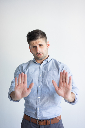 Portrait of serious young Caucasian man showing stop gesture. Businessman wearing blue shirt expressing attitude with rejection sign. Dislike and refusal concept Banque d'images