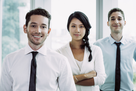 Group of three young business people smiling and standing one after another with office window in background. Woman with her arms crossed is standing between two men.