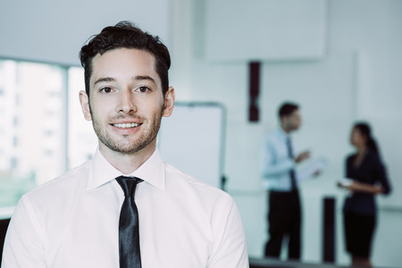 Portrait of young businessman smiling and looking straight with male and female colleagues standing in background and discussing issues