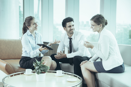 Young businesswoman telling male and female colleagues something. Other woman is holding tablet PC. They are smiling, drinking coffee and sitting on sofa and armchair at table in cafe.