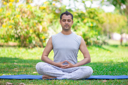 Focused young Indian man meditating in lotus pose. Calm young yogi practicing lesson outdoors in park. Yoga and fitness concept