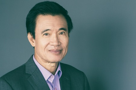 Portrait of confident middle-aged Asian businessman isolated on grey background