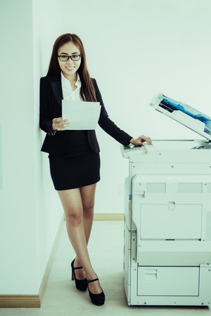 Full-length portrait of young Asian businesswoman wearing glasses standing at copier or multifunction device holding paper, looking at camera and smiling